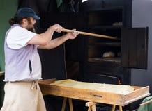 Bagaren sätter bröd på skyffeln in i ugnen royaltyfri fotografi