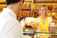 Bagaren shoppar butiksinnehavaren ger bröd till kunden Arkivfoto