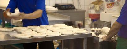 Bagaren som siktar mjöl till och med en sikt i bageri, shoppar arkivfoto