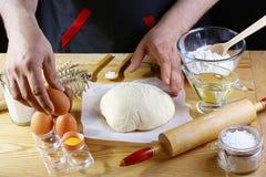 Bagaren tillfogar ägg till ingredienserna för det degbröd-, pizza- eller pajreceptet med händer, mat på köksbordbakgrund som arbe arkivfoto