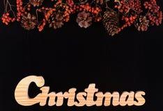 Bagas, cones e escrita secados do Natal em um backg do pinho preto Fotos de Stock Royalty Free