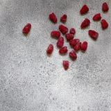 Bagas congeladas das framboesas no fundo concreto cinzento Imagem de Stock