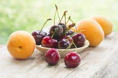 Bagas da cereja doce e dos abricós em uma tabela de madeira Imagem de Stock