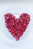 Bagas da romã do close up em uma forma do coração foto de stock royalty free