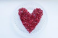 Bagas da romã em uma forma do coração fotografia de stock