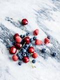 Bagas e cerejas em uma laje de mármore fotos de stock