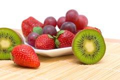 Bagas e fruto maduros suculentos - quivi, morangos e uvas. Imagens de Stock Royalty Free