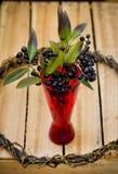 Bagas pretas no vaso vermelho no fundo de madeira Foto de Stock