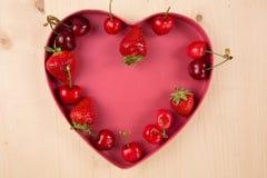 Bagas vermelhas para o dia do Valentim em caixa heart-shaped foto de stock