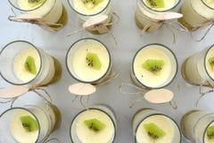 Bagatelle de kiwi en verres avec les cuillères en bois Image stock