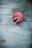 Bagattella brillante rossa del ramo dell'abete sul conce di celebrazioni del bordo di legno Immagini Stock