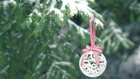 Bagattella di natale bianco che appende sull'albero di abete nevoso video d archivio