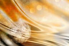 Bagattella di Natale su un oro e su un contesto astratto d'argento con tessuto di seta Fotografia Stock