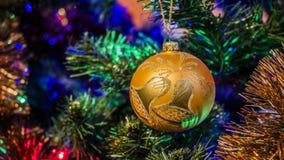 Bagattella dorata sui precedenti di un albero di Natale decorato con le luci di Natale Immagine Stock