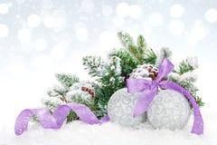 Bagattelle di Natale e nastro porpora sopra il fondo del bokeh della neve Immagini Stock Libere da Diritti