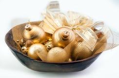 Bagattelle dorate di Natale in una ciotola Fotografia Stock