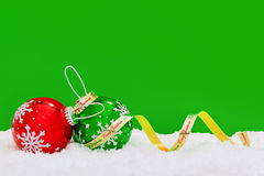 Bagattelle e nastro del fiocco di neve su fondo verde. Fotografia Stock