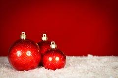 Bagattelle rosse di Natale su neve Fotografia Stock