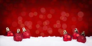 Bagattelle rosse di Natale su neve con un fondo rosso Fotografia Stock Libera da Diritti
