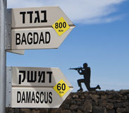 Bagdad damascus. Direction sign with a soldier in the background over blue sky Royalty Free Stock Photos
