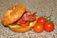 Bagel σπόρου σουσαμιού με τις ντομάτες αμπέλων Στοκ Φωτογραφία