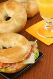 Bagel with bacon, cheese and lettuce and orange juice Stock Photo