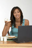 Bagel for breakfast. Woman at computer with bagel Stock Image
