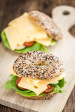 Bagel with Cheese (Gouda). And some fresh vegetables (close-up shot; selective focus Stock Photo