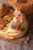 Bagel com ovos mexidos e vertical do close-up do bacon Foto de Stock Royalty Free