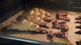 Bagel con le ciliege al forno in forno stock footage