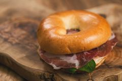 Bagel with coppa and cream cheese on wood boar. D, shallow focus Stock Images