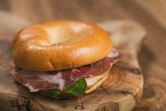 Bagel with coppa and cream cheese on wood boar. D, shallow focus Royalty Free Stock Images