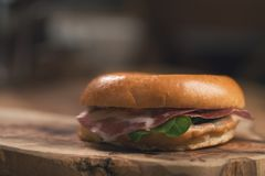 Bagel with coppa and cream cheese on wood boar. D, shallow focus Stock Photo