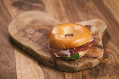 Bagel with coppa and cream cheese on wood boar. D, shallow focus Royalty Free Stock Image