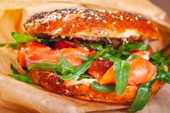 Bagel with cream cheese, smoked salmon and arugula salad in brown paper bag. Close up royalty free stock photos