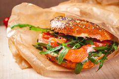 Bagel with cream cheese, smoked salmon and arugula salad in brown paper bag. Close up stock photography