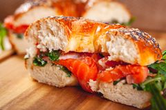 Bagel with cream cheese, smoked salmon and arugula salad cut in half on wooden board. Close up royalty free stock images