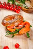Bagel with cream cheese, smoked salmon and arugula salad on wooden board. Close up royalty free stock image