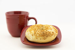 Bagel d'ail avec le plat et la tasse rouges Images stock