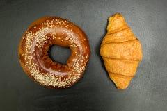 Bagel e croissant freschi su un fondo nero fotografia stock