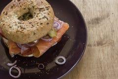 Bagel entier de grain avec le fromage de saumon et fondu, les oignons et les conserves au vinaigre cachères Photographie stock