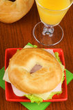 Bagel with ham, cheese and lettuce and orange juice Royalty Free Stock Images