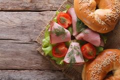 Bagel with ham on an old wooden table top view horizontal Stock Image