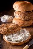 Bagel with Herb Cream Cheese. A delicious whole grain bagel with herbed cream cheese on a rustic wood table royalty free stock photography