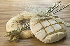 Bagel and loaf. A bagel, a loaf and some wheat on a bamboo mat Royalty Free Stock Photography