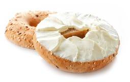 Bagel med gräddost på vit bakgrund Royaltyfria Bilder