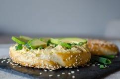 Bagel med hummus, avokadoskivor, kryddor, salladslöken och sesamfrö på svartstenskrivbordet close upp Slapp fokus arkivfoton