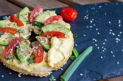 Bagel med hummus, avokadoskivor, kryddor, salladslöken, tomater körsbär och sesamfrö på svartstenskrivbordet close upp arkivfoton