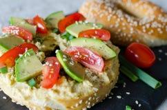 Bagel med hummus, avokadoskivor, kryddor, salladsl?ken, tomater k?rsb?r och sesamfr? p? svartstenskrivbordet close upp arkivbild