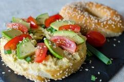 Bagel med hummus, avokadoskivor, kryddor, salladsl?ken, tomater k?rsb?r och sesamfr? p? svartstenskrivbordet close upp arkivbilder
